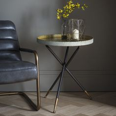Elinor Tripod Table  A unique side table with tripod legs and a high walled table top with a distressed white hammered finish with contrasting gold inside with extra gold detailing at the bottom of the legs.