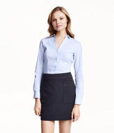 Figurbetonte Bluse aus stretchiger Baumwollmischung. Modell mit V-Ausschnitt und Knöpfen vorn und an den Ärmelabschlüssen.
