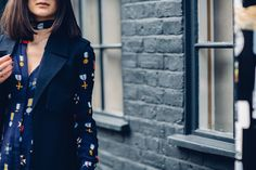 Anisa Sojka styles navy blue Boden midi dress with badges | Long sleeveless coat vest from Fashion Bunker | Mid-wash mom denim jeans | Black Miu Miu cat eye sunglasses | Heeled ankle boots | Brunette straight shoulder length hair let loose | Fashion blogger street style shot in London by Moeez Ali