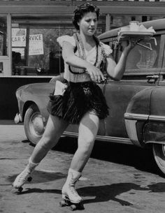 A waitress on roller skates delivers a tray full of food to hungry customers, 1940s