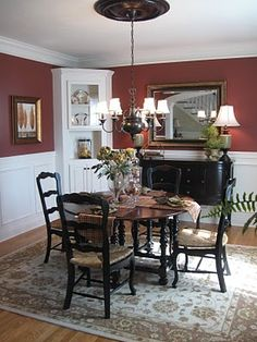 A Charming French Country Dining Room White wainscoting, dark chairs, black buffet with mirror, area rug