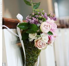 Pink, green, and purple floral arrangements hung at the end of each row, accenting the bride's path.