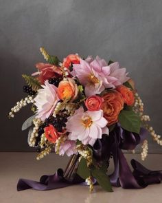 Soft-hued dahlias, roses, ranunculus, and andromeda are complemented by dark fruit