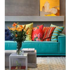 O bom dia de hoje vai acompanhado de muita cor. A base cinza da parede serviu de pano de fundo para o sofá turquesa e para um bouquet de flores em forma de almofadas. Ameiii!!!!!!!
