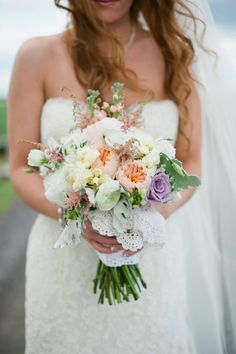 peach yellow and purple wedding bouquet wrapped in lace