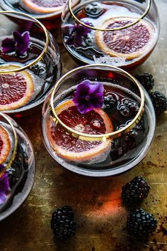 Blood Orange Blckberry Rum Punch / 4 (12 ounce) chilled natural blackberry sodas, natural / 1 cup Blackberries, fresh / 1 cup Blood orange, juice / 1 Blood orange / 1/4 cup Lime juice, fresh / 1 cup Rum / pansies to garnish (optional)