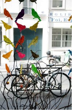 colorful paper birds in shop window display.
