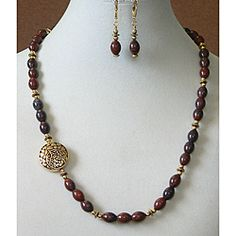 Featuring oval jasper beads, this elegant earring and necklace set is adorned with gold beads and a filigree-accented oval pendant. This handmade jewelry set features leverback and toggle clasp closur