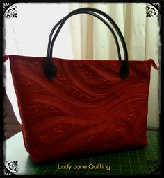 Completed bag, free motion quilting with black and red Isacord thread on red leatherette, red satin lining, one inside pocket, zipper and black leatherette handles. Quilted on Bernina Q20, assembled on Bernina 720. #berninarsa #berninaambassador #ladyjanequilting #freemotionquilting