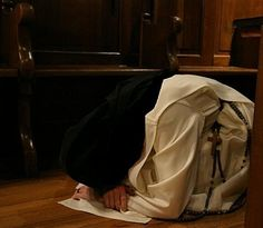 Dominican nun praying in the middle of the stalls of the church
