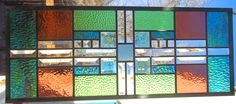 Stained Glass Window Transom I like this but I would trade the square for a diamond shape Also put less color to match the front door and side lights Hang between the LR and DR as free hanging pane or built in