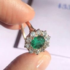 Antique Victorian cluster engagement ring is set with a carat oval-cut emerald surrounded by 10 old European-cut diamonds weighing approximately carats total. Set in yellow gold. Raw Stone Jewelry, Jewelry Rings, Fine Jewelry, Jewellery, Diamond Cluster Engagement Ring, Engagement Rings, Emerald Ring Vintage, Emerald Ring Gold, Ruby Diamond Rings