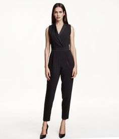 Sleeveless jumpsuit in woven fabric with a slight sheen. Notch lapels in satin with concealed snap fastener at front, seam at waist with a wide band, and concealed side zip. Decorative chest pocket, side pockets, and mock back pockets. Wide, tapered legs with pleats at waist and satin stripes at sides. Unlined.