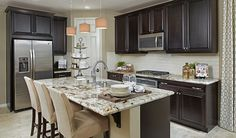 This Inviting Kitchen In Palmdale, CA, Boasts Neutral Granite Countertops,  A Spacious Center