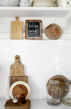 the wood-framed chalkboard, wood chopping boards, clear unadorned glass canisters, and plain white ironstone