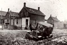 """Happy Throw Back Thursday! Stuck in the Mud, Stacey Avenue and Court Street, 1915.This photo aptly illustrates the traditional comment that accompanied the coming of the automobile - when the car wouldn't go, someone was bound to say """"get a horse"""". In this view of a car mired to the axles in mud, a horse hitched to an unseen vehicle looks on. While downtown streets were paved in 1911, it was some years later before the side streets were done."""