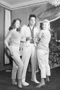 Elvis Presley 22 holds the two lady friends Cathy Gabriel and blonde Hannerl Melcher who was 'Miss Austria' in 1957.Both will enjoy Christmas with Elvis at Graceland in 1957.Hannerl Melcher was a show girl who met Elvis in Oct 1957 when he was in Las Vegas