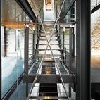 Rising to a catwalk above, a huge glass-and-steel central stair envisioned by the architect spans four floors of the Chiavellis' newly expanded house.