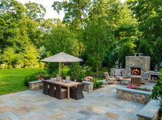 jardin contemporain aménagé avec une cheminée extérieure en pierre, un salon de jardin en bois et rotin et un dallage en pierre