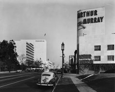 Vintage cars and streetlights line the sidewalk in front of the Arthur Murray dance studio at Wilshire and Curson, 1948.