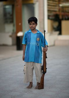 Boy with a Barcelona UNICEF shirt holding a gun in Salalah - Oman by Eric Lafforgue, via Flickr