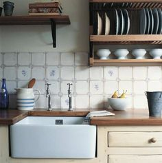 Wpuszczony w masywny drewniany blat duży ceramiczny zlew sprawdzi się przy myciu dużych naczyń, a także warzyw czy owoców. Wystrój tej wiejskiej kuchni jest spójny: ręcznie dekorowane kafle, drewniana zabudowa, tradycyjna półka-suszarka na talerze. Osobny kran na zimną i ciepłą wodę – klasyczne angielskie rozwiązanie – chętnie zastępujemy baterią z mieszalnikiem, bardziej w zgodzie z naszymi zwyczajami.