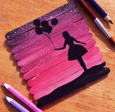 Silhouette of a girl holding Balloons. Made by putting popsicle sticks together and painting them pink/purple.