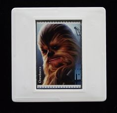 """In 2018 the Royal Mail released a set of special stamps featuring some of the favourite droids, aliens and creatures of the Star Wars films. This 1st class stamp design shows Chewbacca, nicknamed """"Chewie"""", the loyal friend and first mate of Han Solo, and serves as co-pilot on Solo's spaceship, the Millennium Falcon. He first appeared in Star Wars in 1977. The unused stamp is encased in a vintage slide mount, with glass, making this a unique piece of jewellery. The Loyal, Star Wars Film, Han Solo, Millennium Falcon, Chewbacca, Royal Mail, Design Show, Postage Stamps, Aliens"""