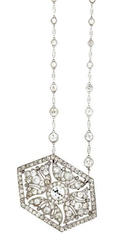 An art deco diamond pendant brooch, Cartier, circa 1920, with diamond chain   comprising a pierced and openwork pavé-set diamond hexagonal plaque, centering an old European-cut diamond; and a fancy link chain, interspaced with collet-set diamonds; pendant brooch signed Cartier, Paris, Londres, New York; center diamond in brooch weighing approximately: 0.90 carat; estimated remaining diamond weight: 0.65 carat; mounted in platinum; brooch length: 1 3/4in; chain length: 15in. Via Bonhams.