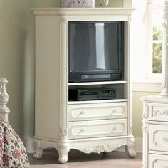 """Homelegance Cinderella White TV Armoire for Girls by Homelegance. $616.44. Floral motif hardware. Ecru painted finish. Belongs to Cinderella Collection. Victorian styling. Traditional carving details. Features: TV Armoire has solid wood construction Ecru Finish Two drawers One shelf Perfect for girls Specifications: Overall Dimensions: 54.75"""" H x 35.25"""" W x 18.5"""" D Overall Weight: 126 lbs Manufacturer Limited 90-Day Warranty Minor Assembly Required. Save 31% Off!"""