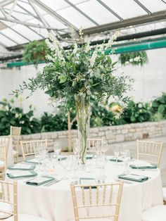 Tall and airy centerpiece of foliage and white blooms for a guest table at wedding at the Philadelphia's Horticultural Center