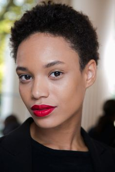 "Makeup artist Dick Page offset glowy skin with a ""very 80's and fun"" red lip. To get the look, Shiseido The Perfect Rouge in Dragon. - ELLE.com"