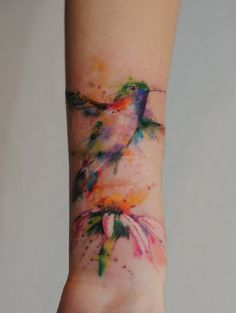 hummingbird watercolor forearm tattoo with flower - petals, feather