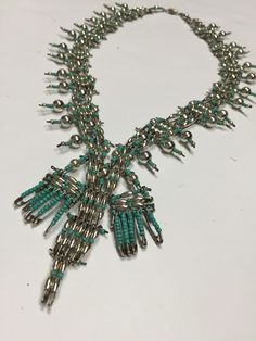 This 1970s safety pin squash blossom necklace is reminiscent of the mid-century fad of constructing jewelry from safety pins. This authentic