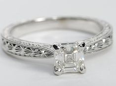 Breathtakingly unique engagement ring in white gold with delicately detailed hand engraving on the band. The center diamond that you choose to set in this ring will look great with the accents around the ring.