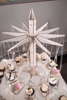 FOOD and DECORATION: This is one of the coolest things I think I've ever seen. Cupcake Holder  Carnival style swings hold 12 by CleverlyBuilt, $159.00