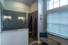 This spacious master bathroom includes a partial glass enclosed walk-in shower with neutral textured walls and a pebble tile floor. A window seat boasting neutral granite is located just outside of the shower, providing a convenient spot for toweling off.