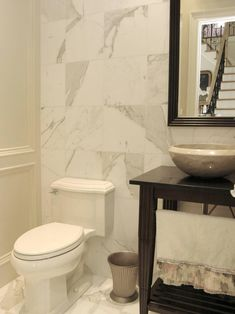 Trimmed in white, this powder room is accented with rich dark wood, classy marble walls and flooring.