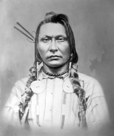 Chief Crow, Crow, head and shoulders studio portrait; braids wrapped in fur, earrings. Photo by David F. Barry