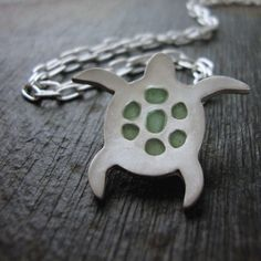 """Whether you love the beach or simply mother nature, you will love this sea turtle slide pendant. This stunning turtle silhouette is handmade with eco-friendly pure reclaimed fine silver. To further decorate this beautiful tortoise shell I filled each cavity with hand-tinted minty green resin.  Measurements: Slightly over 1"""" x 3/4""""  Included is an 18 inch curb link chain. (I can shorten the length of the necklace if you would like).  All of my necklaces are delivered via first class mail…"""