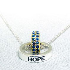 Enduring hope linked circle necklace. Hope is the thing that keeps us moving. Above everything else, belief in the future endures and the world endures with it. The color of the planet and the sky, blue is a constant in this world. Surrounding us everyday and pushing us to move forward, the act of hope is just as constant. Let the eternal circles of this pendant remind you to always keep your hopefulness. A blue colored crystal encrusted gold circle sits within a solid silver circle…