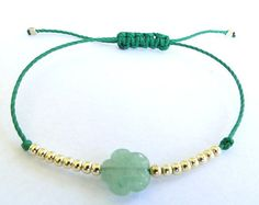 Bracelet made with gold beads and jabe flower bead.    They make a nice bracelet helped by a waxed thread. This listing is for one bracelet!    It is made in green waxed thread. Adjustable Knot great for any size of wrist.    Contact me if you want other colour!    Thank you for looking