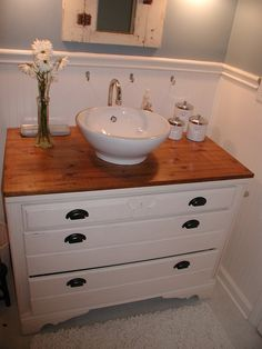 From my old house. I turned a $10.00 dresser into a bathroom vanity. Added a wood top that I sealed, bowl sink, added new sides that made the dresser appear deeper to accommodate the pipes, trimmed it with molding. Painted it all, changed hardware and cut into the back of the drawers so pipes fit. I may do this again if I can find a small enough dresser. I miss that vanity! -Chrysti