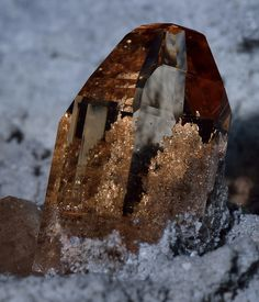 A beautiful Topaz crystal on a block of matrix. The top half is nearly eye-clear. The matrix behind the crystal turns golden and looks as though it is within the stone.