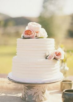 Simple but elegant wedding cake. The few flowers maintain its elegance. More imp...