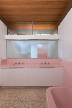 """""""The three original bathrooms were each designed in a different pastel color: pink, yellow, and blue,"""" says Cole. These were mostly intact, though the homeowners reinstalled the colored Crane toilet in the master bath, pictured above. The restorers polished the original terrazzo flooring."""