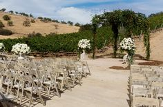 Leigh and Alex's ceremony guests found their seats at rustic wooden chairs. A tall ceremony structure made of branches and vines was flanked on both sides by stone urns filled with ivory blooms. #weddingceremony #decor Photography: Elisabeth Millay Photography. Read More: http://www.insideweddings.com/weddings/romantic-neutral-hued-wedding-at-a-paso-robles-california-vineyard/585/
