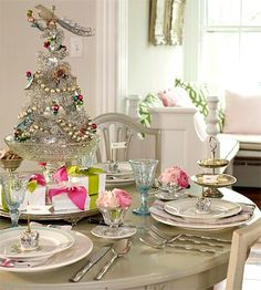 The key to any glitzy Christmas table is pops of silver and pink. A small silver tree atop a glass compote makes room for wrapped favors below. Vintage ice cream dishes make wonderful vases filled with pink ranunculus. For festive flair, wrap napkins with silver and pink ribbon and tuck them between mismatched dinner plates. Dainty crowns sitting on the plates fly flags touting seating arrangements.