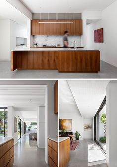 This modern kitchen features American Walnut wood cabinets, white countertops and a stone backsplash. Polished concrete floors and white walls complete the modern interior.