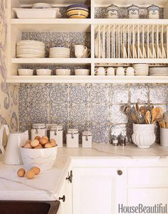 Above the countertops and stove of this California kitchen by designer Erin Martin, the backsplash is clad in a romantic blue-and-white French tile from Country Floors.